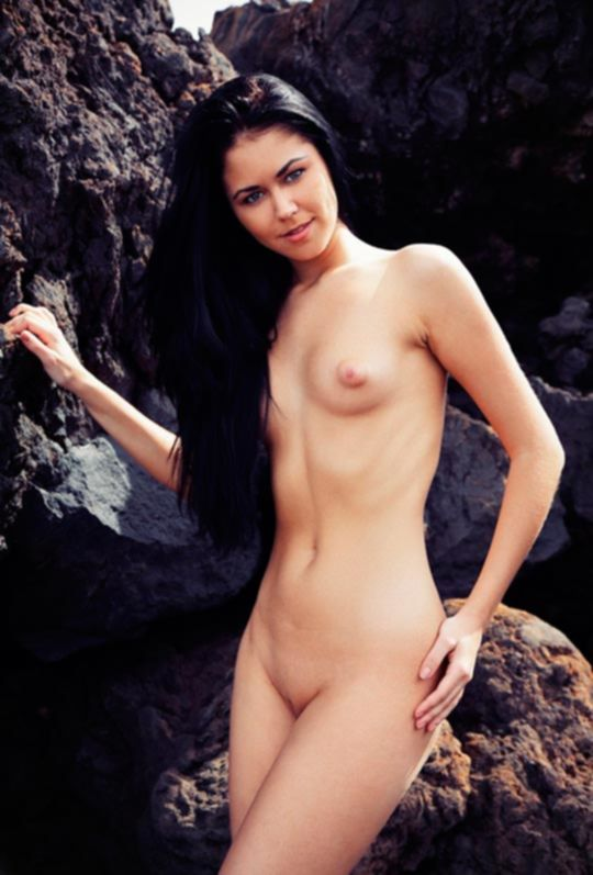 Молодая брюнетка на скалистом берегу моря