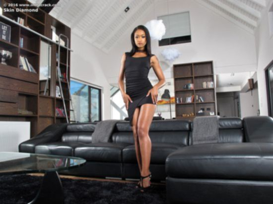 Смуглая актриса Skin Diamond в черном платье растопырила ножки на диване