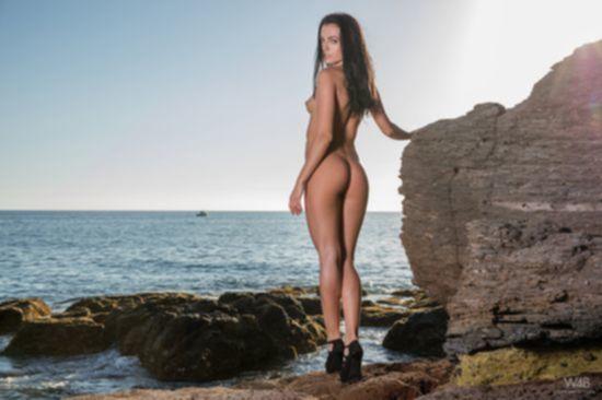 Прекрасное женское тело Sapphira A на каменистом береге моря